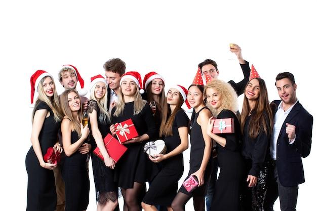 新年や休日を祝うコンセプト。スタイリッシュな黒い服とサンタの帽子をかぶった若い美しい人々のグループ。ギフトボックスを手に楽しんでいます。