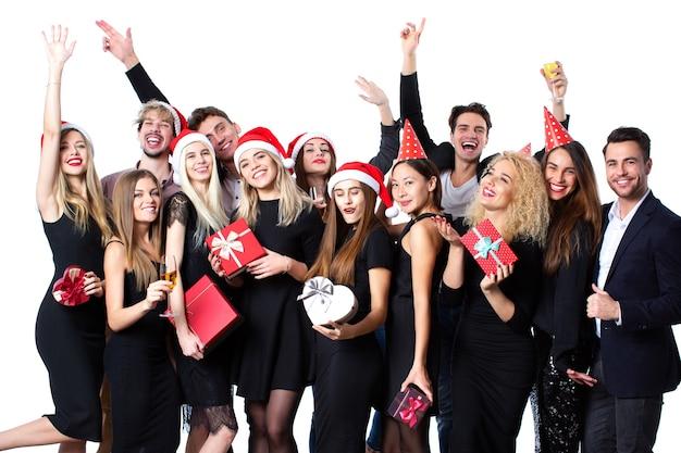 새해 또는 휴일을 축하하는 개념. 세련 된 검은 옷과 재미 손에 선물 상자 산타 모자에 아름 다운 젊은이의 그룹입니다.