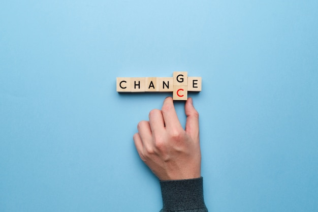 The concept of change and chance. hand picks up letters on a yellow background.