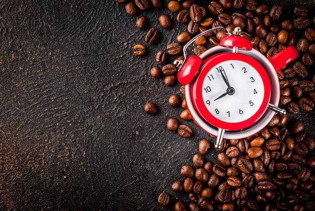 Concept of a cheerful, good start to the day, morning coffee. dark rusty background with coffee beans, an alarm clock and a cup of coffee. top view copy space