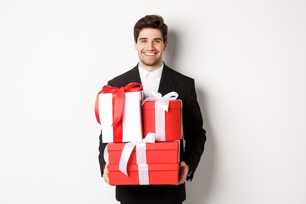 Concept of christmas holidays, celebration and lifestyle. image of attractive boyfriend in black suit, holding gifts and smiling, wishing happy new year, standing over white background.