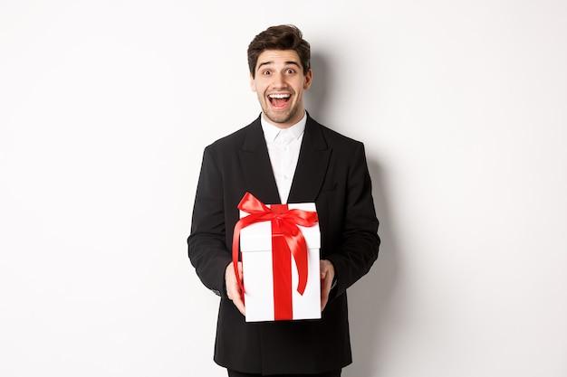 Concetto di vacanze di natale, celebrazione e stile di vita. immagine di un bel ragazzo in abito nero che sembra eccitato, ha un regalo, in piedi su sfondo bianco