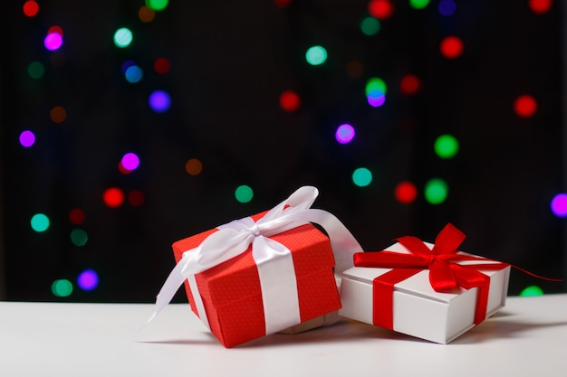 The concept of christmas and new year gifts on the table against the background of blurry lights bokeh