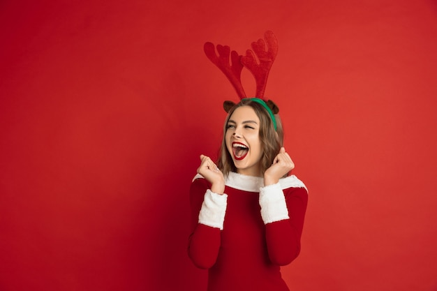 Concept of christmas, new year's, winter mood, holidays. beautiful caucasian woman with long hair like santa's reindeer catching giftbox.