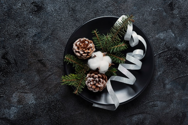 Concept of christmas table decoration on black background, top down view