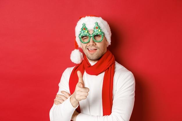 Concetto di natale, vacanze invernali e celebrazione. primo piano del giovane sfacciato con cappello da babbo natale e occhiali da festa, sorridente e puntando la pistola con il dito in telecamera, in piedi su sfondo rosso.