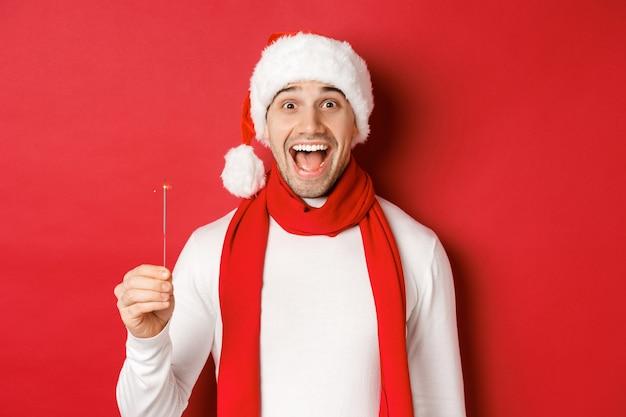 Concetto delle vacanze invernali di natale e primo piano di celebrazione dell'uomo bello felice in cappello di babbo e ...