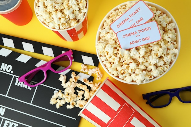 Concept of cinema accessories on yellow background.
