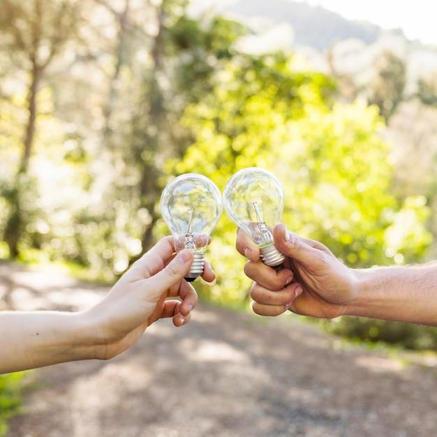 Lampadine tintinnanti concetto nelle mani in natura