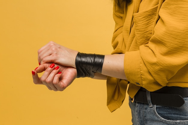Концепция крупным планом фото женщины-жертвы с заклеенным ртом, похищение. носит желтую рубашку, изолированный желтый цвет фона.