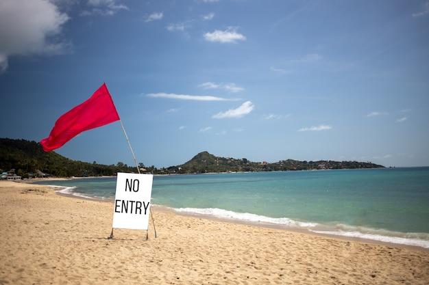 コンセプトクローズドビーチ、プライベートビーチ、動作していません。晴れた日には空の熱帯のビーチに立ち入り禁止の赤い旗と看板があります