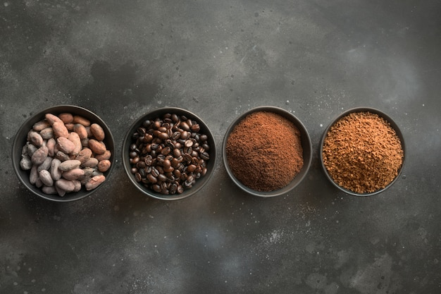 Concept of cocoa and coffee beans in bowls on dark.