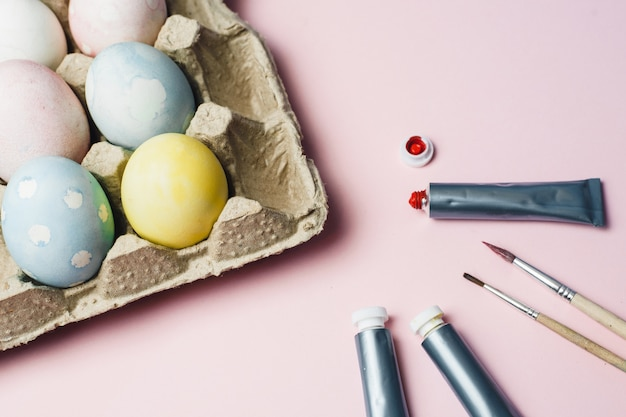 The concept of coloring easter eggs in pastel watercolor colors. paints and brushes for coloring eggs for easter on pink background
