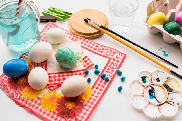 Concept of coloring eggs on napkins near palette and brushes