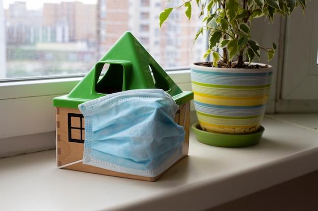 コンセプトは検疫covidモードに準拠医療マスクのおもちゃの家は次の窓辺に立っています