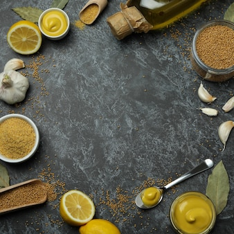 Concept of cooking mustard on black smoky background, space for text
