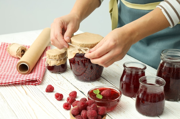 Concept of cooking raspberry jam on white wooden table.