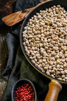 The concept of cooking roasted chickpeas with pink pepper. healthy vegetarian food. dark background. top view