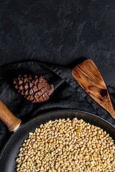 Concept of cooking roasted pine nuts in a frying pan. top view