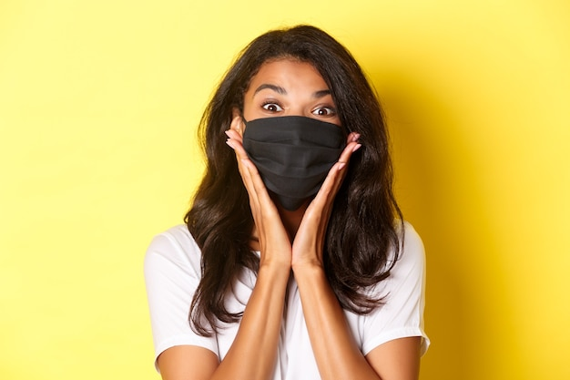 Concept of coronavirus, pandemic and lifestyle. close-up of amazed african-american girl in black face mask, looking wondered at something awesome, yellow background.
