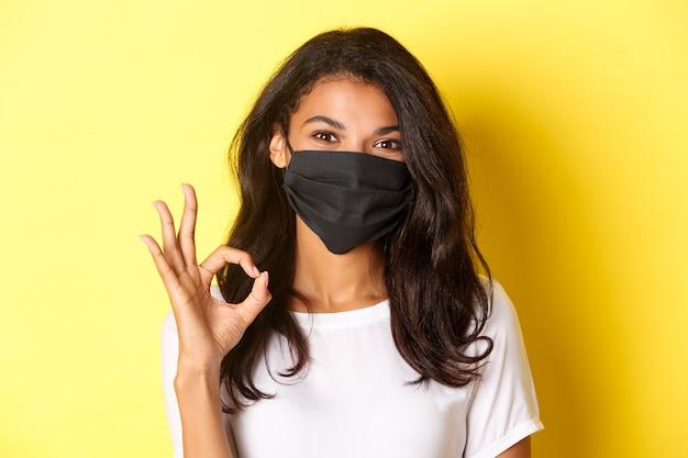 Concetto di coronavirus, pandemia e stile di vita. primo piano di una bella donna afroamericana in maschera nera, che mostra il segno giusto in approvazione, loda il buon lavoro, sfondo giallo.