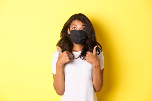Concept of coronavirus, pandemic and lifestyle. portrait of beautiful african-american girl in black face mask, showing thumbs-up in approval, like something good, yellow background.