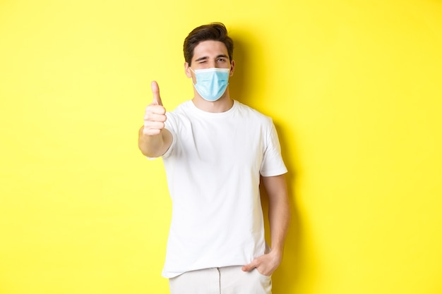 Concept of coronavirus, pandemic and social distancing. confident young man in medical mask showing thumbs up and winking, yellow background.