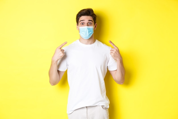 Concept of coronavirus, pandemic and social distancing. young surprised man pointing at medical mask on face, yellow background. copy space