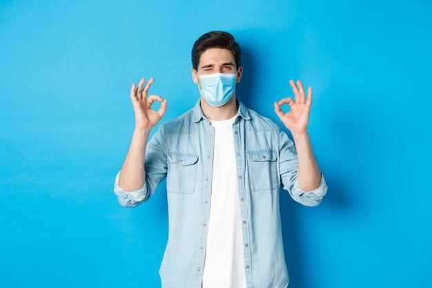 Concetto di coronavirus, quarantena e distanziamento sociale. uomo sfacciato in maschera medica che fa l'occhiolino, mostra segni ok, assicura o garantisce qualcosa, piace e approva