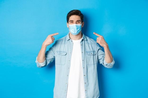 Concetto di coronavirus, quarantena e distanziamento sociale. bell'uomo che punta alla maschera medica e sorride, protezione dalla diffusione del virus durante la pandemia, sfondo blu.