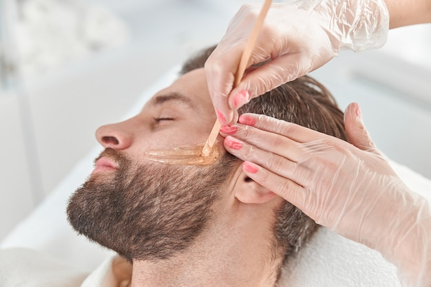 Concept of cosmetology and facial. a woman beautician makes face and beard modeling for a man waxing epilation. depilation with wax.