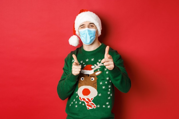 Concept of covid-19 and christmas holidays with handsome young man wearing a mask