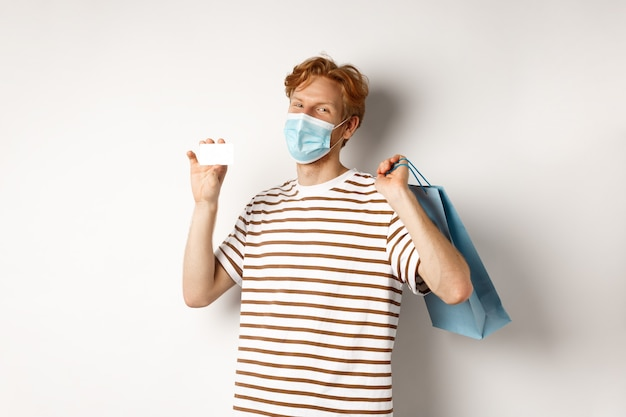 Concept of covid-19 and lifestyle. happy young shopper in face mask holding shopping bag and showing plastic credit card, buying with discounts, white background