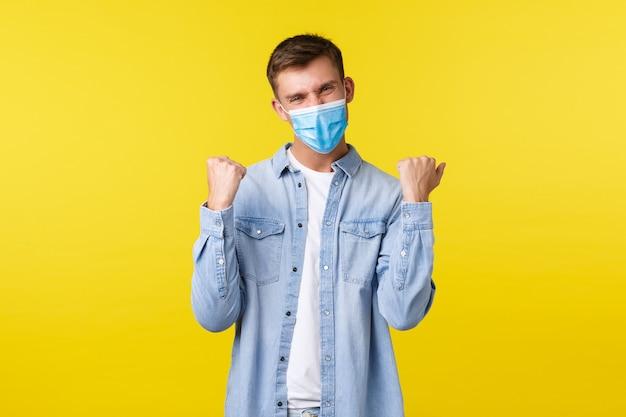 Concetto di epidemia di pandemia di covid-19, stile di vita durante l'allontanamento sociale del coronavirus. bel ragazzo felice in maschera medica, pompa a pugno e dicendo di sì, gioendo per la vittoria, sentendosi fortunato.