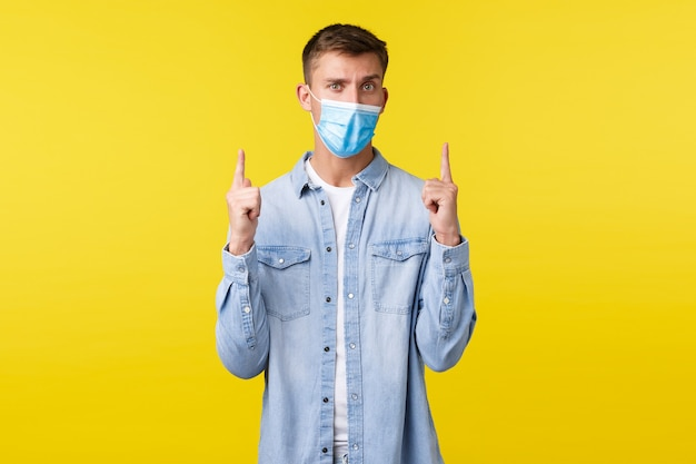 Concept of covid-19 pandemic outbreak, lifestyle during coronavirus social distancing. suspicious and confused guy in medical mask, looking doubtful and pointing fingers up, yellow background.