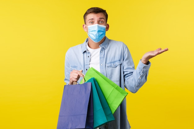 Concept of covid-19 pandemic outbreak, shopping and lifestyle during coronavirus. confused and clueless cute indecisive man in medical mask, carry bags with purchased items and shrugging.