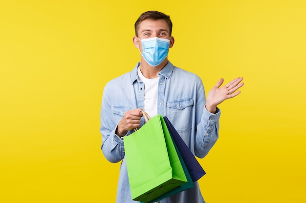 Concept of covid-19 pandemic outbreak, shopping and lifestyle during coronavirus. handsome happy young man in medical mask enjoying buying things in store, holding bags with presents.