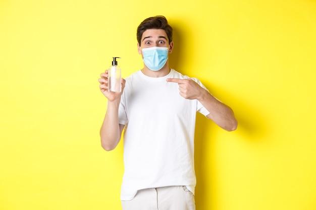 Concetto di covid-19, quarantena e stile di vita. ragazzo eccitato in maschera medica che mostra un buon disinfettante per le mani, puntando il dito contro l'antisettico, in piedi su sfondo giallo