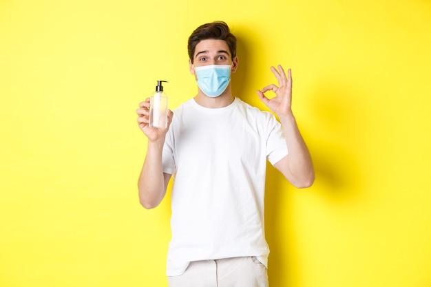 Concetto di covid-19, quarantena e stile di vita. giovane soddisfatto in maschera medica che mostra un buon disinfettante per le mani, fa un segno ok e raccomanda antisettico, sfondo giallo.