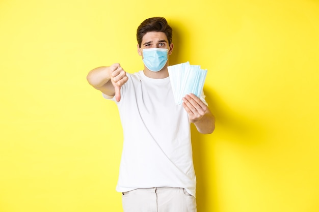Concept of covid-19, quarantine and preventive measures. man looking disappointed and showing thumb down, do not recommend bad medical masks, standing over yellow background.