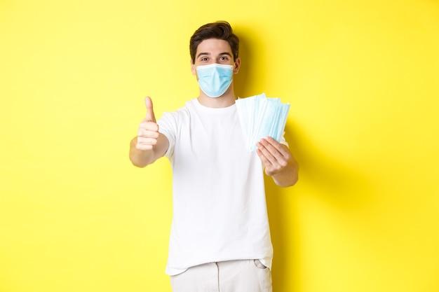 Concetto di covid-19, quarantena e misure preventive. uomo soddisfatto che mostra pollice in su e dà maschere mediche, in piedi su sfondo giallo.