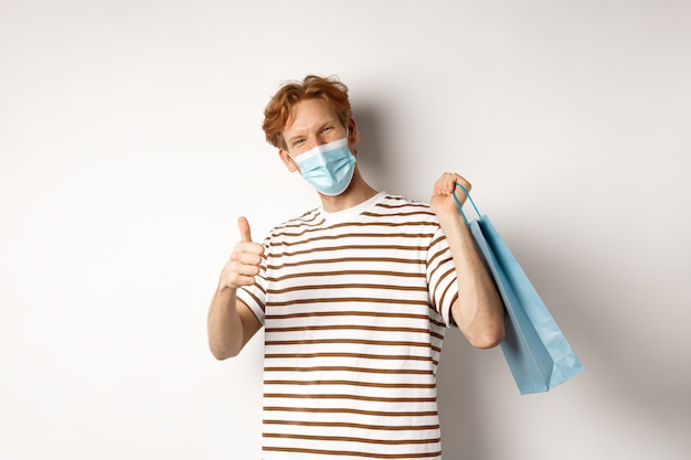 Concept of covid-19 and shopping. satisfied young man looking pleased after shopping, wearing face mask, showing thumbs-up, recommend store, white background.