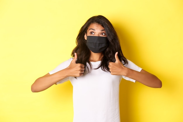 Concetto di covid-19, distanziamento sociale e stile di vita. immagine di allegra ragazza afro-americana in maschera nera, che mostra il pollice in su e sembra felice nell'angolo in alto a sinistra, sfondo giallo.