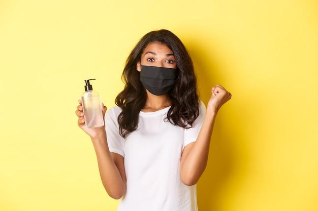 Concetto di covid-19, distanziamento sociale e stile di vita. immagine di una donna afroamericana felice in maschera facciale, felice di aver fondato un buon disinfettante per le mani, rallegrandosi su sfondo giallo