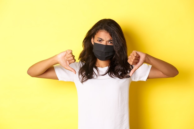 Concept of covid-19, social distancing and lifestyle. image of upset african-american female protester, wearing black face mask, showing thumbs-down and frowning disappointed, yellow background.