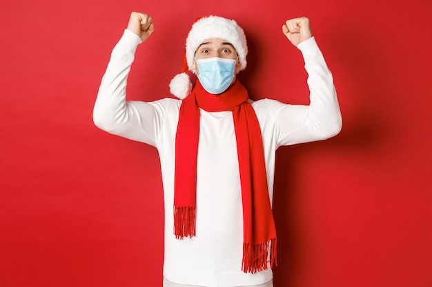 Concetto di covid natale e vacanze durante la pandemia ritratto di un uomo felice con cappello da babbo e medico...