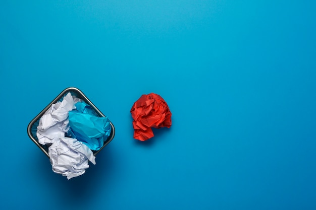 Concept. creased paper in a trash can on blue background