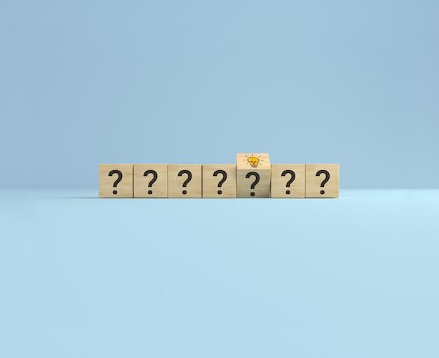 Концепция творческой идеи и новаторства. переверните деревянный кубик со знаком вопроса и значком лампочки. искра