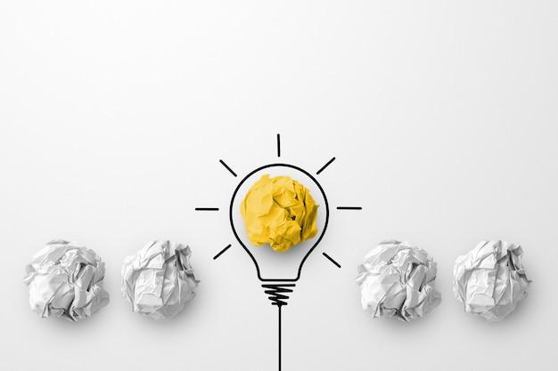 Концепция творческой идеи и новаторства. бумажный шарик желтого цвета, выдающаяся разная группа с символом лампочки