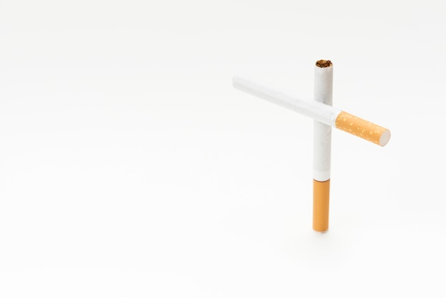 Concept of cross sign made from cigarette on white background